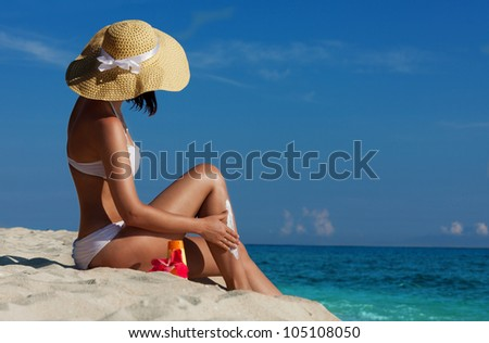 Slim happy woman on the beach applying sunscreen to her legs - stock photo