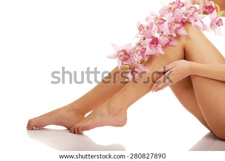 Slim long woman legs with pink flowers. - stock photo