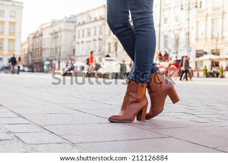 Slim model legs in blue jeans. Autumn fashion creation. On the background of city - stock photo