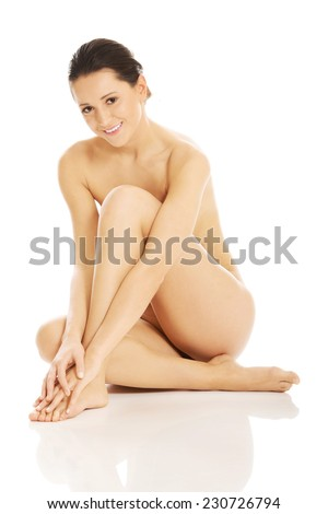 Slim nude woman sitting on the floor - stock photo