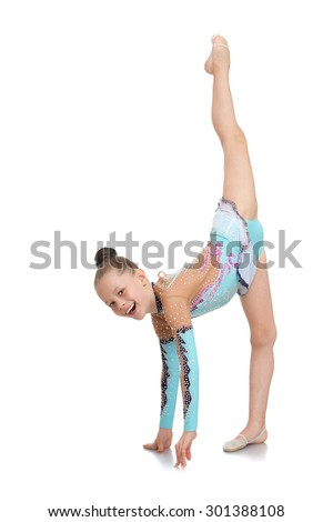 Slim pretty young girl athlete with hair combed into a ball standing on one leg and doing the splits while still laughing. A girl dressed in a beautiful sport swimsuit-Isolated on white background - stock photo