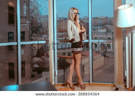 Slim sexual blonde woman drinks tea near the large window with city views. Business woman drinks tea. City views behind the window. Business concept. - stock photo