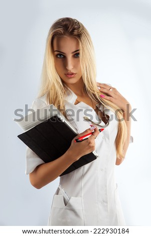 Slim sexy nurse seduce in studio on grey background - stock photo