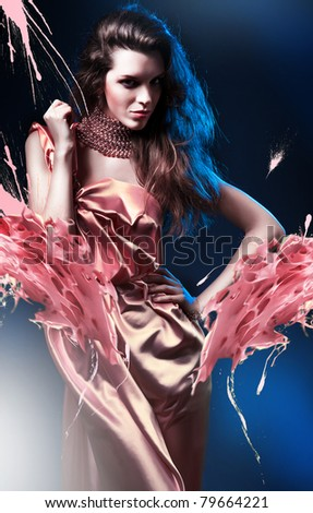 slim sexy woman in pink dress on blue light and splash - stock photo
