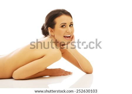 Slim spa woman lying on belly against the floor