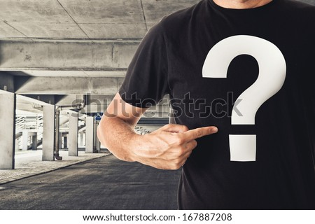 Slim tall man posing in black t-shirt with question mark in public garage