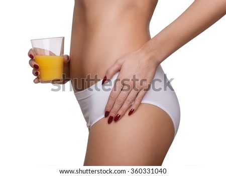 Slim tanned woman's body. Isolated on white background, orange juice in hand - stock photo