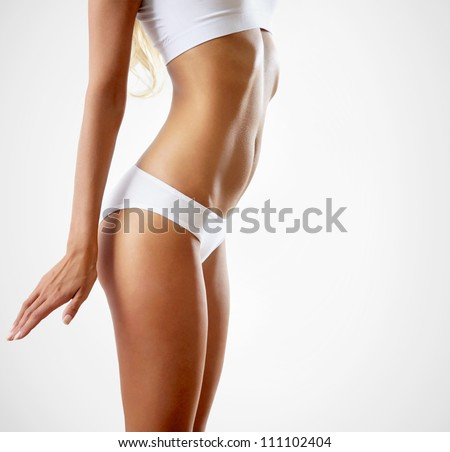 Slim tanned woman's body. Isolated over gray background. - stock photo
