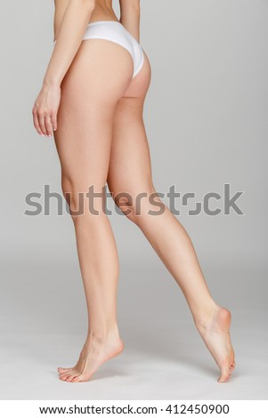 Slim tanned woman's body Isolated over gray background - stock photo