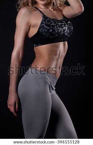 Slim tanned woman's body over dark grey background