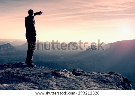 Slim tourist on the sharp peak of rock in rock empires park  is watching over the misty and foggy morning valley to Sun - stock photo