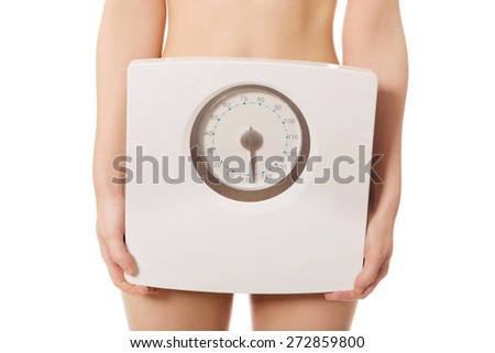 Slim undressed woman holding a scale. - stock photo