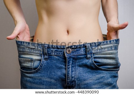 Slim Waist of Young Woman thin body with perfect, showing her jeans after successful diet or fitness, Weight loss and slimming concept. - stock photo