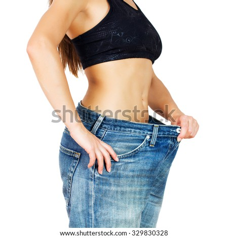 Slim Waist of Young Woman with perfect healthy thin body,showing her old jeans after successful diet. Unrecognizable person.Weight loss and slimming concept. - stock photo