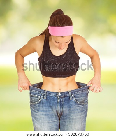 Slim Waist of Young Woman with perfect healthy thin body,showing her old jeans after successful diet. .Weight loss and slimming concept. - stock photo