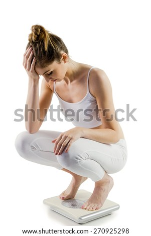 Slim woman disappointed on scales on white background - stock photo