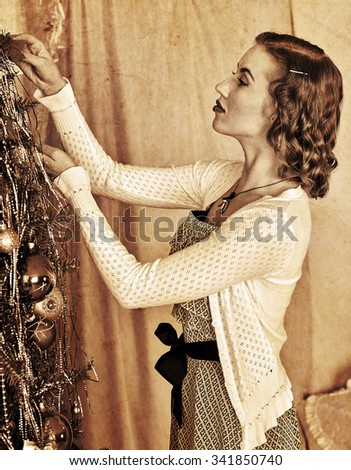 Slim woman dressing Christmas tree. Black and white vintage style. - stock photo