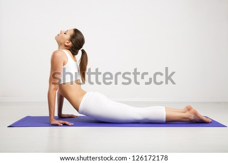 Slim woman exercising on a mat in a gym - stock photo