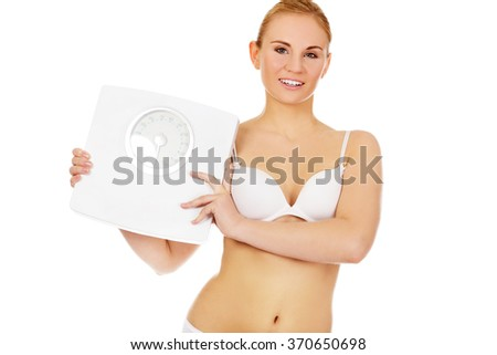 Slim woman holding a weight scales - stock photo