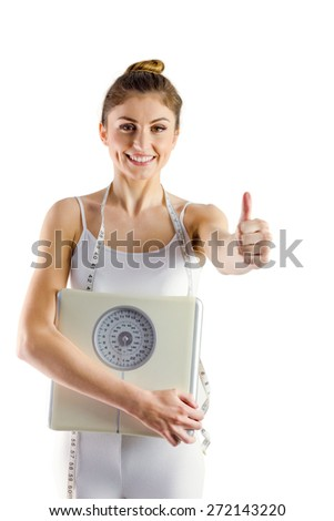 Slim woman holding scales and measuring tape on white background - stock photo