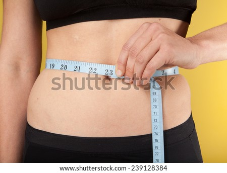Slim woman in black underware measuring her waist - stock photo