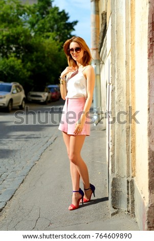 Slim woman in sunglasses standing on hot summer street. Pretty girl posing in old town in Europe.