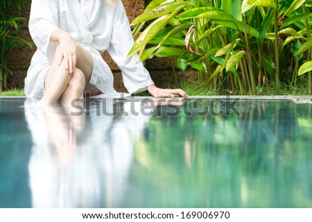 Slim woman in white bathrobe sitting at pool in hotel with her feet in blue clear water. Fresh and natural atmosphere with green plants around. Hotels and resorts. Spa procedures and healthcare.