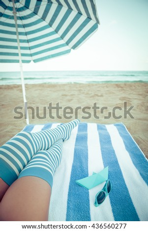 Slim woman legs on a beach. Summer vacation and travel concept