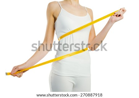 Slim woman measuring her waist on white background - stock photo