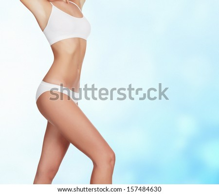 Slim woman on blue blurred background.  - stock photo