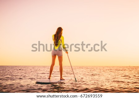 Slim woman on stand up paddle board with beautiful sunset or sunrise colors