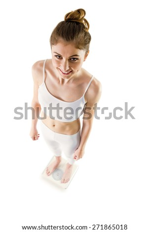 Slim woman standing on scales on white background - stock photo