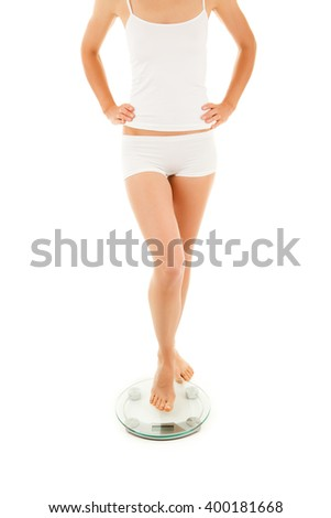 Slim woman standing on weight on white background