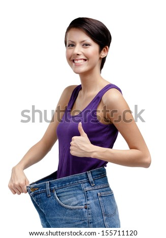 Slim woman wearing big jeans, isolated on white - stock photo