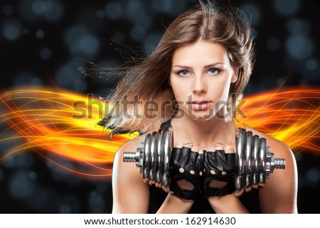 Slim woman with dumbbells, black background - stock photo