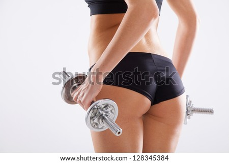 Slim woman with dumbbells, white background - stock photo