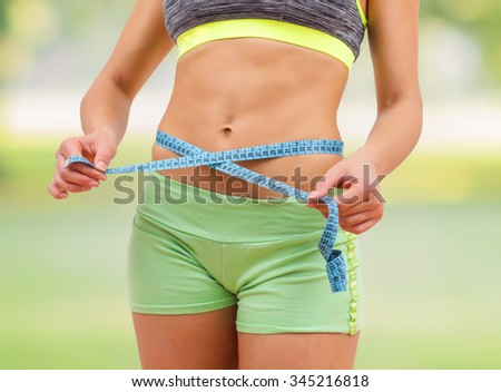 Slim Woman with perfect healthy fitness body, measuring her thin waist with a tape measure. Unrecognizable person.Diet and weight loss concept. - stock photo