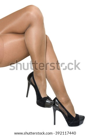Slim women's legs in pantyhose and black shoes isolated on white background - stock photo