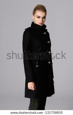 Slim young cute fashion model in a black coat posing on gray background - stock photo