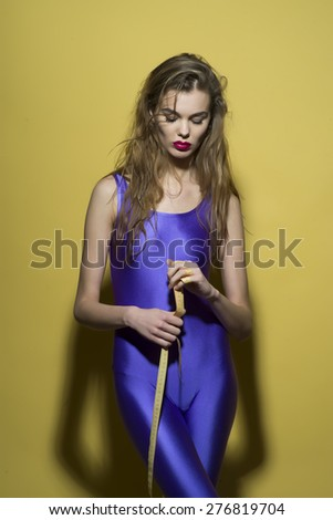 Slim young girl in violet second skin jumpsuit holding tape-line standing on yellow background, vertical picture - stock photo