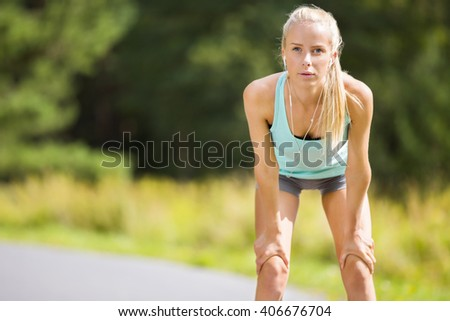 Slim young woman catching her breath after a long run - stock photo