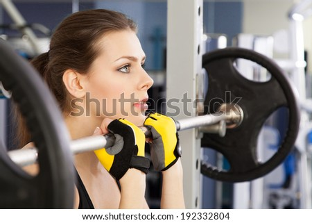 Slim young woman exercising in a gym - stock photo