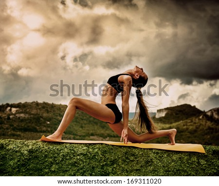 Slim young woman makes warrior yoga pose  - stock photo