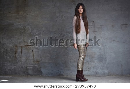 Slim young woman with long brown hair in shiny grey clothes posing over grey background - stock photo