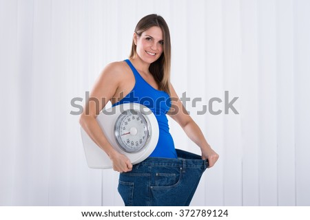 Slim Young Woman With Weighing Machine Wearing Big Jeans