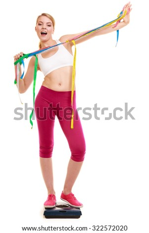Slimming and weight loss. Happy joyful young woman girl holding tape measures on weighing scale. Healthy lifestyle concept. Isolated on white. - stock photo