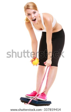Slimming diet weight loss. Happy joyful satisfied young woman girl with measuring tape on weighing scale holding apple isolated on white background. Healthy lifestyle concept. - stock photo