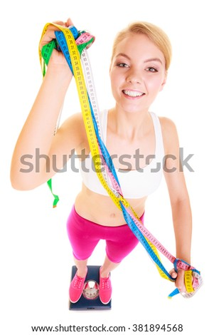 Slimming diet weight loss. Happy joyful young woman girl holding tape measure on weighing scale. Healthy lifestyle concept. Isolated on white background.  - stock photo