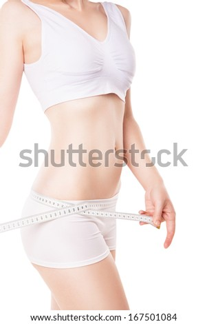 slimming woman measuring her hip with measuring tape over white background