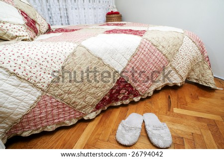 Slipper near the bed with floral bedding - stock photo